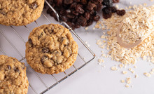 Cinnamon Raisin Oatmeal Cookies With Ingredients On A Marble Counter