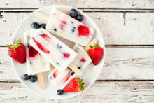 Healthy Strawberry Blueberry Yogurt Ice Pops On A Plate, Top View Against A White Wood Background