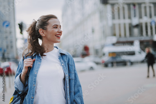 Pretty smiling young female walking around city