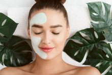 Facial Mask. Girl Lying On Table With Tropical Leaves