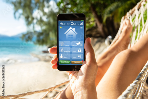 Fotografia Woman Using Smart Home On Mobile Phone At Beach