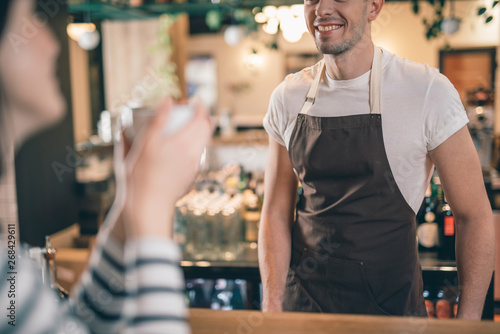 Close up of smiling male barista at the bar counter