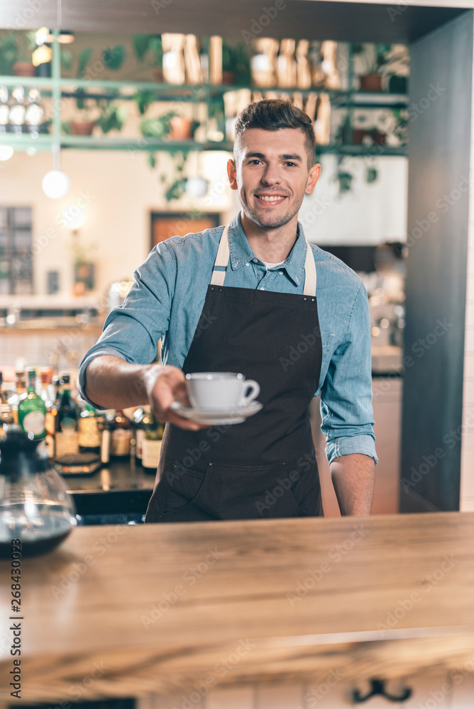Fototapeta Friendly barista giving cup of coffee and smiling