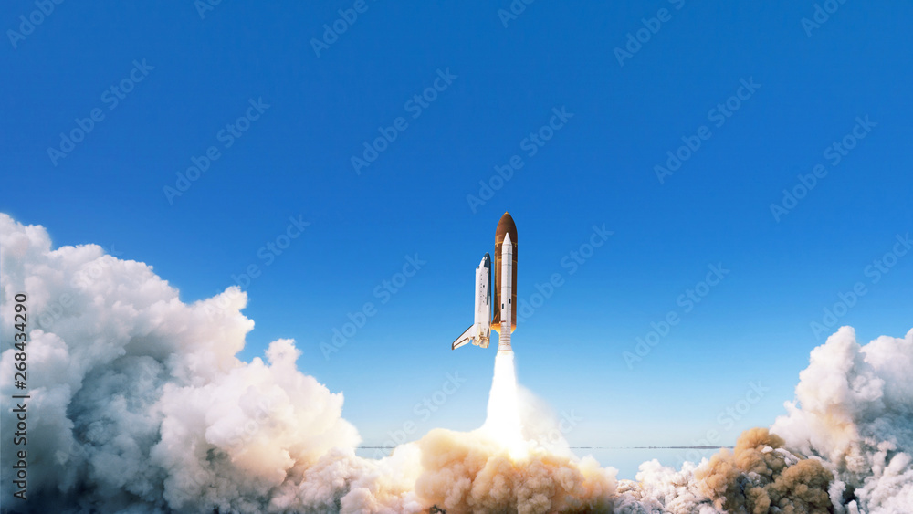 Fototapeta Spacecraft takes off into space. The rocket starts in the blue sky. Travel concept