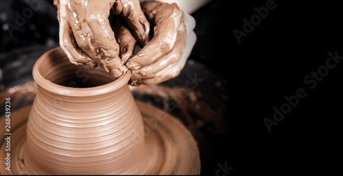 Foto  Hands of potter making clay pot