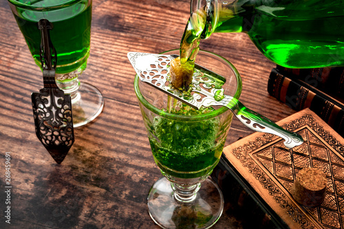 Poster de jardin Bar Alcoholic drink, creative stimulant and bohemian lifestyle concept theme with a vintage glass bottle pouring absinthe over a sugar cube in a stainless steel spoon next to books on a wooden table