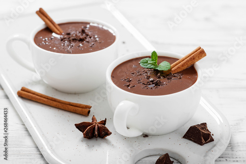 Hot chocolate drinks and chocolate pieces in white cup.