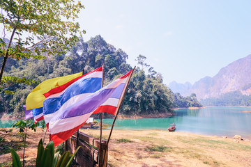 Khao Sok National Park, Surat Thani, Cheow Lan Lake. Flag of Thailand on the beautiful lake background. Concept of Travel in Thailand,