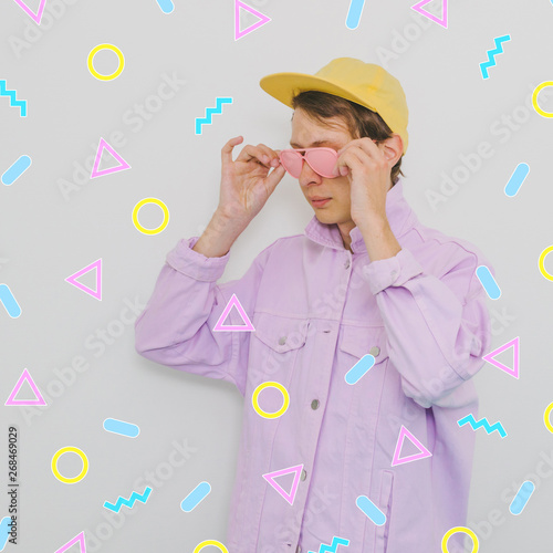 Fotografia  fashionable male model in pink painted sunglasses, baseball cap and lilac jean jacket among memphis geometry figures