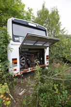 An Old And Abandoned Bus Standing In Bushes.