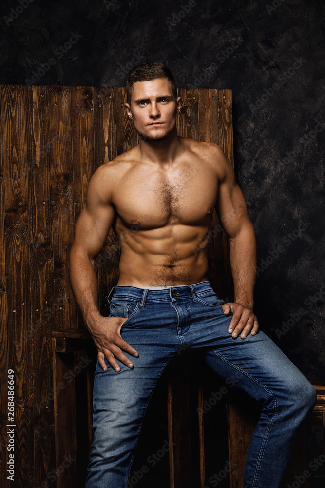 Fototapeta Portrait of handsome muscular and sexy man wearing jeans