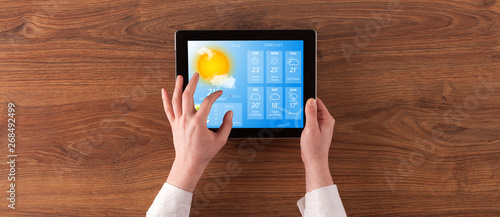 Obraz Man hand checking weekly weather forecast on tablet  - fototapety do salonu