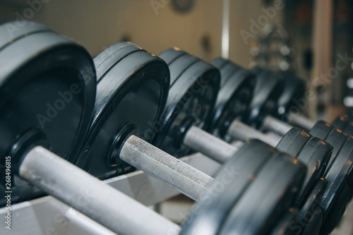 hand metal dumbbells lie together in a row on the rack in the gym close-up. training tools