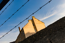 Old House Or Factory With A High Chimney Behind A Barbed Wire Wall