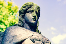 Weathered Statue Of An Angel With Cracked Dirty Face (with A Spider) Covered With Moss At Old Cemetery - Cross Processed Image