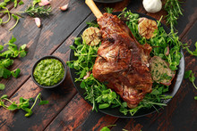 Roast Lamb Leg With Mint Sauce, Rosemary And Garlic. On Black Plate, Wooden Table