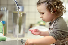 Kid Washing Dishes In Kitchen Sink. Early Development Of Toddler. Baby Girl Learns Household.