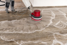 Floor Cleaning With A Machine. A Man Is Cleaning A Tiled Floor In An Apartment.
