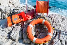 Orange Lifebuoy With Rope And Life Jacket On The Rocks Near Sea