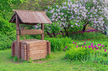 Wooden Well Against The Background Of Blooming Lilacs. Wooden Well In The Countryside.