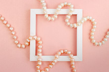 White Square Frame With Pearl Beads On A Pink Pearl Design Board.