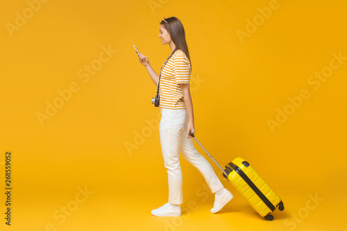 Full-size portrait of European girl isolated on yellow background walking with s Canvas