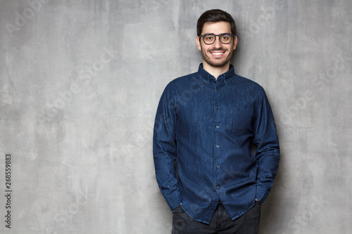 Fotografía  Young handsome male smiling and feeling confident, standing against textured wal