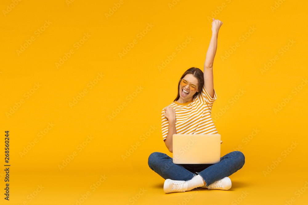 Fototapeta Winner! Excited smiling girl sitting on floor with laptop, raising one hand in the air is she wins, isolated on yellow background