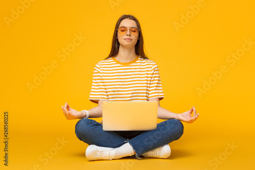 Young woman sitting on floor with laptop meditating in yoga lotus pose isolated on yellow background