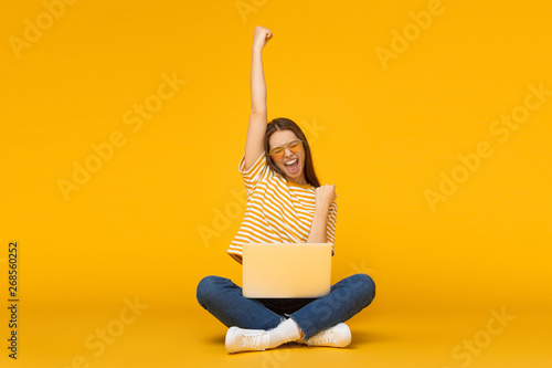 Fotografía She is a winner! Excited young female with laptop isolated on yellow background