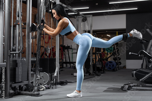 Fotobehang Ezel Fitness woman doing exercise for glutes, cable kickbacks. Athletic girl workout at the gym. Beautiful butt in leggings