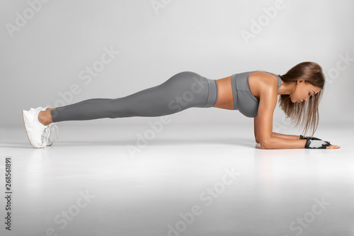Fitness woman doing planking exercise, workout. Slim athletic girl training, isolated on the gray background.