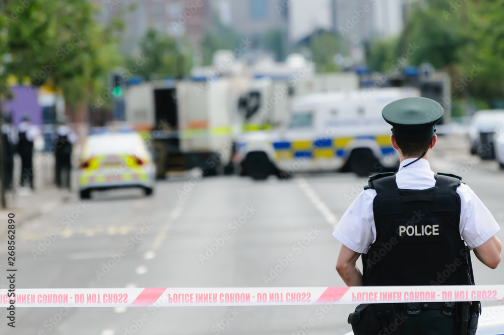 Fototapeta Police officer stands guard at a Police cordon point while army ATOs deal with a suspect bomb.