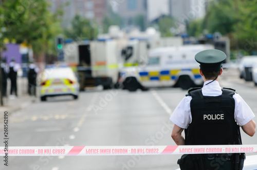 Pinturas sobre lienzo  Police officer stands guard at a Police cordon point while army ATOs deal with a suspect bomb