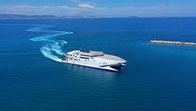 Aerial Drone Top View Photo Of High Speed Passenger Ferry Arriving At Port Of Mykonos Island, Cyclades, Aegean Sea, Greece