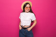 Leinwandbild Motiv Pleased asian young woman in straw hat and sunglasses posing over pink background