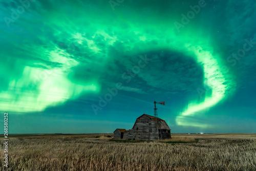 Foto auf Gartenposter Nordlicht Swirl of bright Northern Lights over vintage barn, bins, windmill and stubble in Saskatchewan