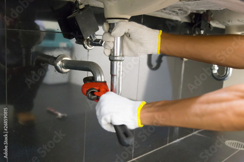 Fotografia, Obraz Plumber fixing white sink pipe with adjustable wrench.