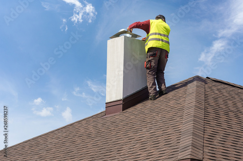 Valokuva Man install chimney on roof top of new house under construction
