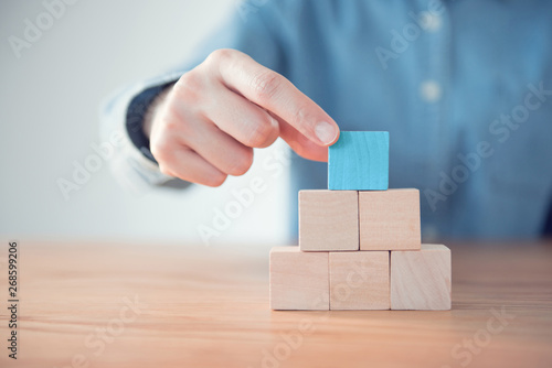 Photo  Hand putting blank blue wood cube block on top pyramid, for create icon symbol to success concept