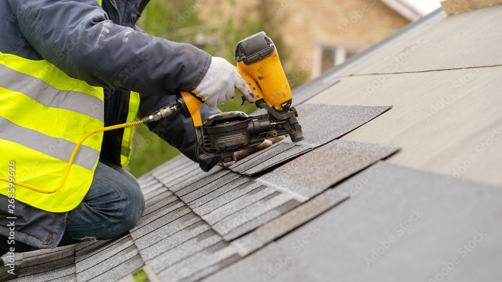 Fototapety, obrazy: Workman using pneumatic nail gun install tile on roof of new house under construction