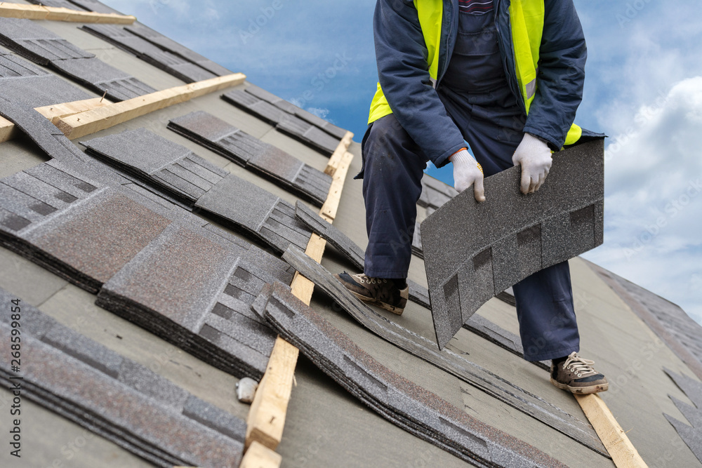 Fototapety, obrazy: Workman install tile on roof of new house under construction