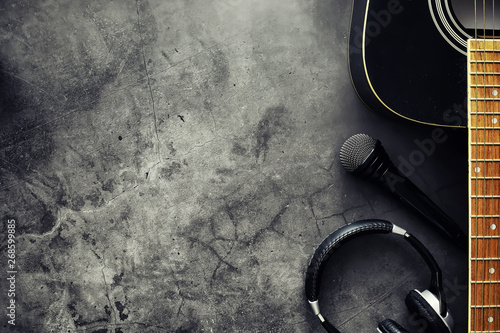 Guitar and accessories on a stone background. Desk musician, headphones, microphone. - 268599885