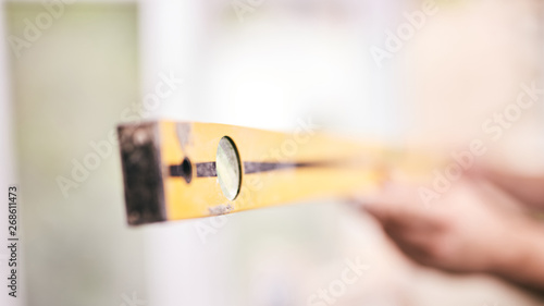 Worker using bubble level for walls inside the house - renovation fixes.