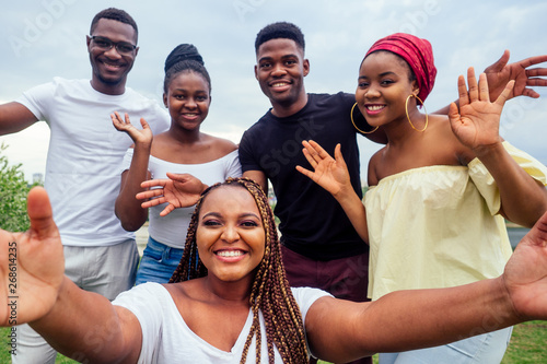 Obraz group of five friends female and male taking selfie on camera smartphone and having fun outdoors lifestyle near lake - fototapety do salonu