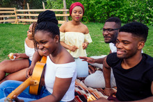 Group Of Smiling Happy Afro-american Friends Friends Playing Guitar Outdoors Picnic In The Campaign