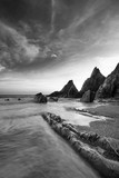 Stunning sunset landscape image of Westcombe Beach in Devon England with jagged rocks on beach and stunning cloud formations - 268619045