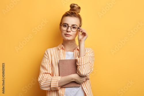 Cuadros en Lienzo  clever cute awesome woman holding a book, touching her glasses and posing to the camera