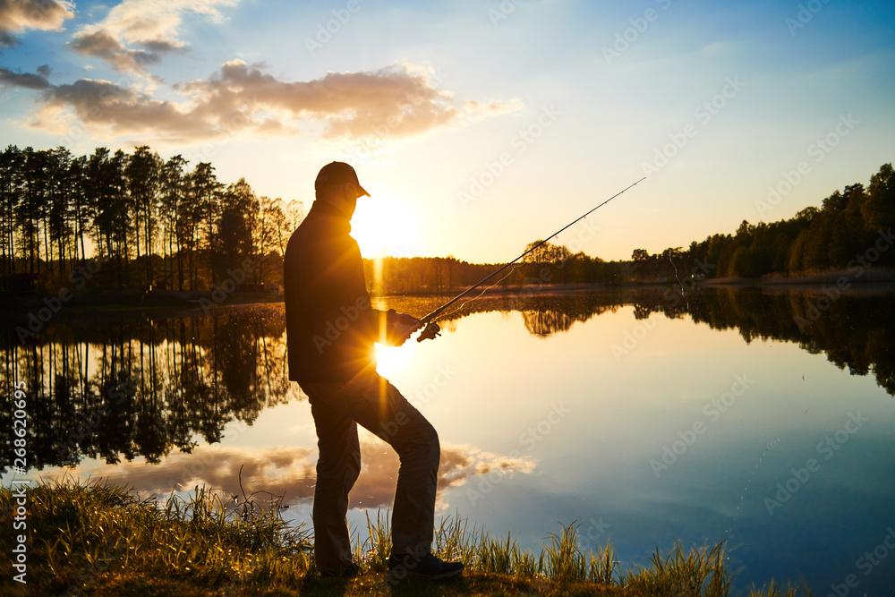 Fototapeta sunset fishing. fisher with spinning rod