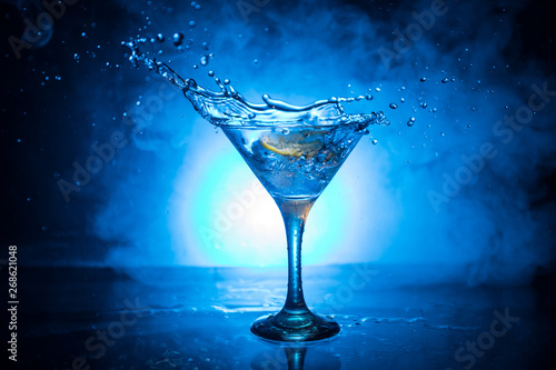 Fotomural  Martini cocktail glass in hand splashing on dark toned smoky background or colorful cocktail in glass with splashes and olives